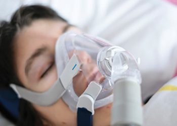 A woman sleeping in her bed with a ventilator